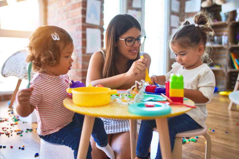 Teacher playing with two pre-school students