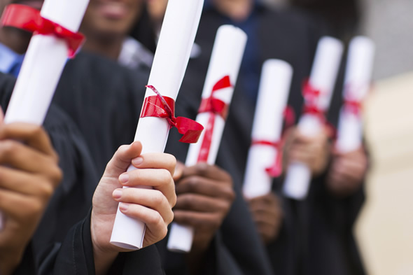 students in graduation robes holding diplomas