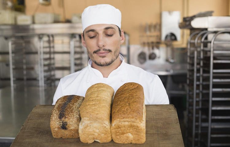A baker in front of various loaves of bread