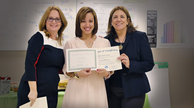 Three women in front of a classroom whiteboard, with one woman holding a certificate of completion