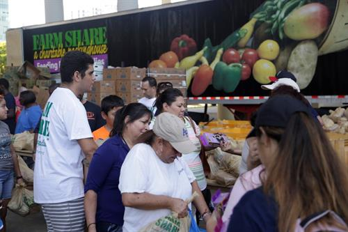 People receiving free food and other helpful items during a distribution event.