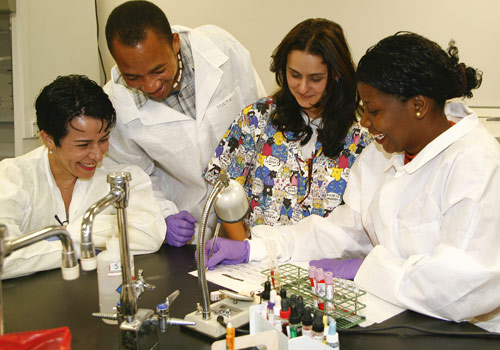 Rosa Castro, an assistant professor of clinical laboratory technology (multi-colored scrubs) works with biologists from Mozambique.