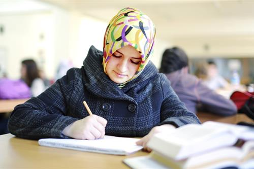 A Muslim woman studying in a library.