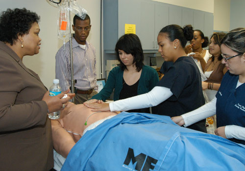 Nursing students receive instruction on a human patient simulator