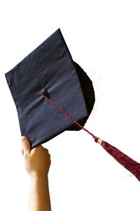 Hand holding up graduation cap
