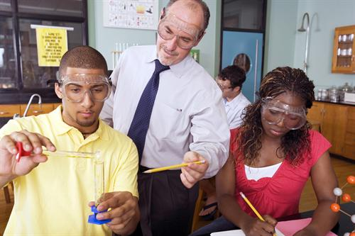 Students performing lab experiment with teacher watching
