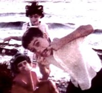 Home movie still showing children on a beach.