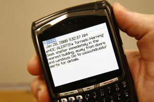 Person holding cellphone with screen displaying MDC alert