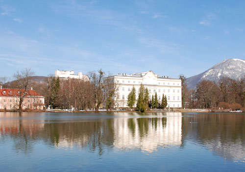 The historic Leopoldskron Palace, nestled by a small lake and offering majestic mountain views.