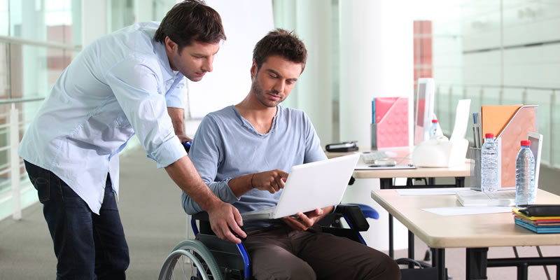 A man in a wheelchair speaks to a coworker at his desk