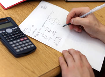 Picture of a student working on a math problem with the focus on his hands and the paper