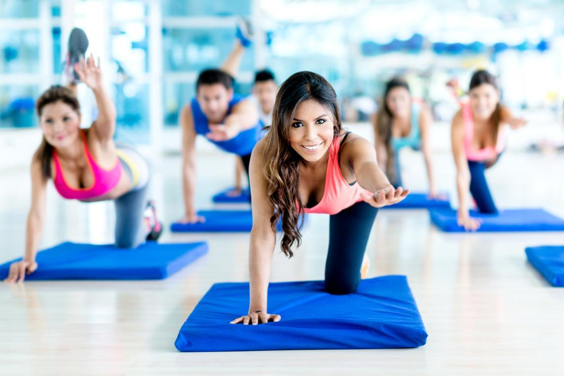 woman featured doing yoga on yoga mat in a class