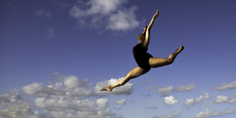 Dancer leaps with the sky in the background