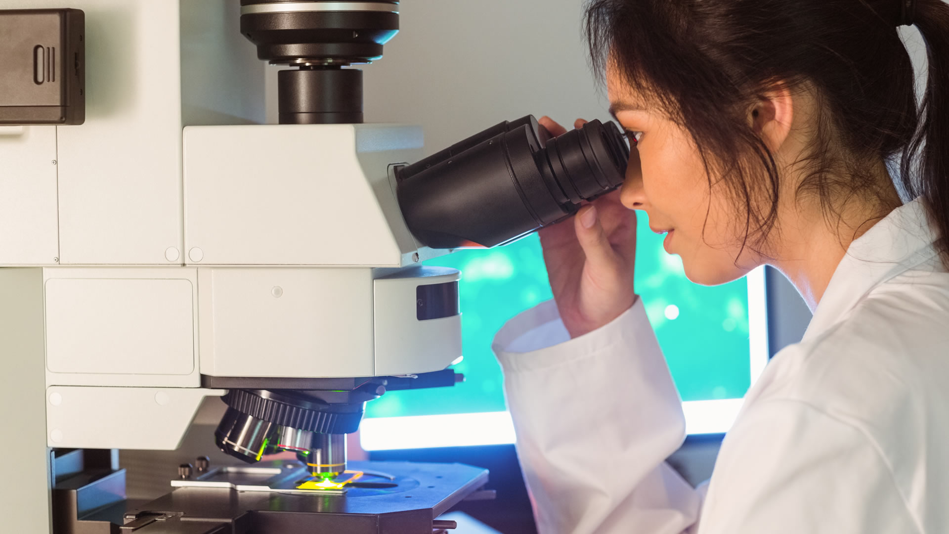 A female student practices using a power electron microscope
